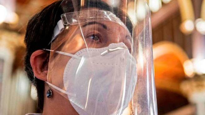 Coronavirus, una donna indossa dispositivi di protezione (Ansa)