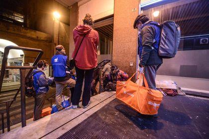 Un giro dei volontari della Comunità di Sant'Egidio a Genova. Sotto, la preparazione dei pasti alla mensa di via Dandolo a Roma