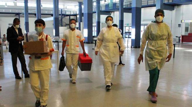 Operatori sanitari indossano tute e mascherine protettive per effettuare controlli su  215 passeggeri bangladesi del volo speciale della Biman Bangladesh Airlines (Bg4165) appena arrivato a Fiumicino da Dacca, Roma, 6 luglio 2020. Ansa/Telenews