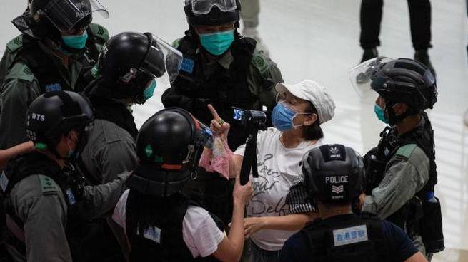 Una donna protesta con gli agenti a Hong Kong (Ansa)