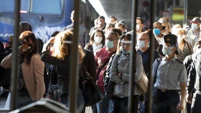 Passeggeri alla stazione Termini con la mascherina (Ansa)