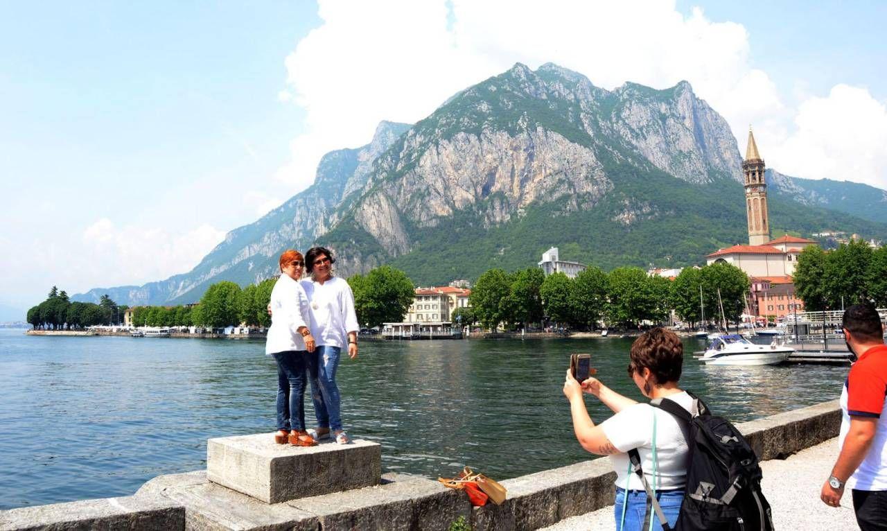 Turisti in posa per una fotografia con il panorama del lago e delle montagne