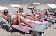 Tre ragazze prendono il sole in spiaggia senza mascherine: voglia di respirare aria pulita in riva al mare