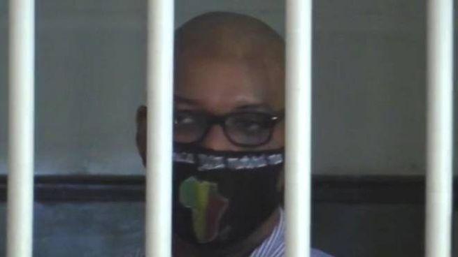 Ousseynou Sy con la mascherina dietro le sbarre nell'aula bunker