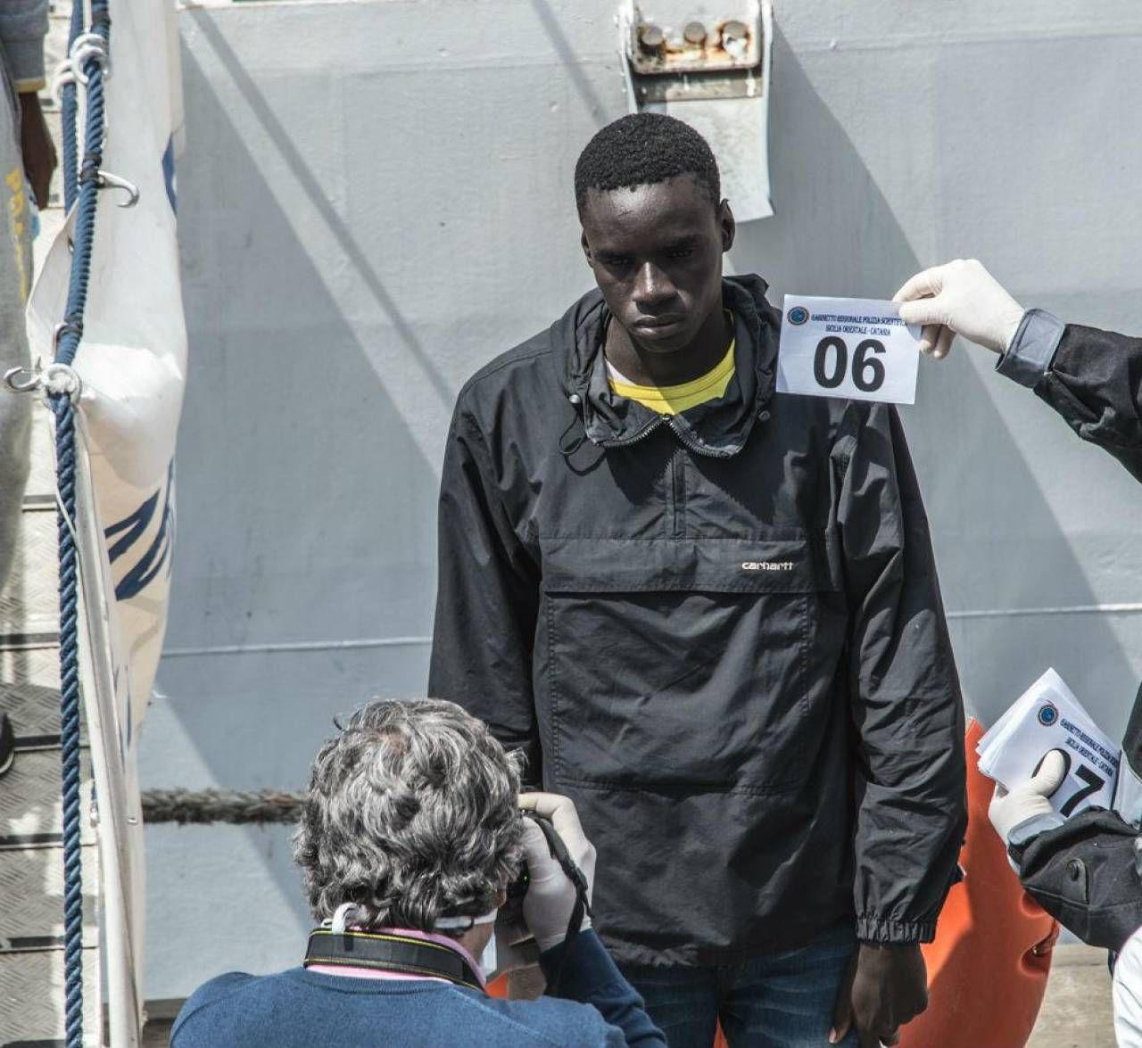 Migranti identificati dalla polizia appena dopo lo sbarco in Italia su uno dei barconi degli scafisti