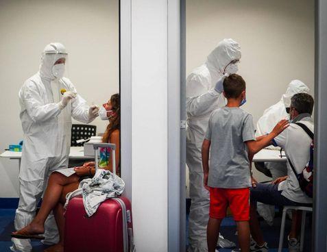 Controlli anti Coronavirus ai passeggeri che transitano dall'aeroporto Capodichino di Napoli. Sotto, il virologo Giorgio Palù