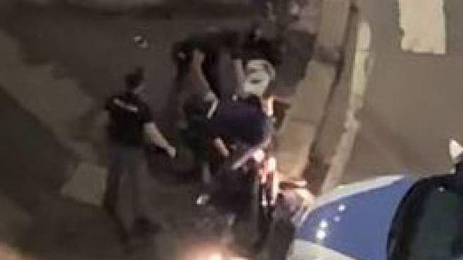 Il momento in cui l'agente colpisce con un calcio uno dei due arrestati a terra