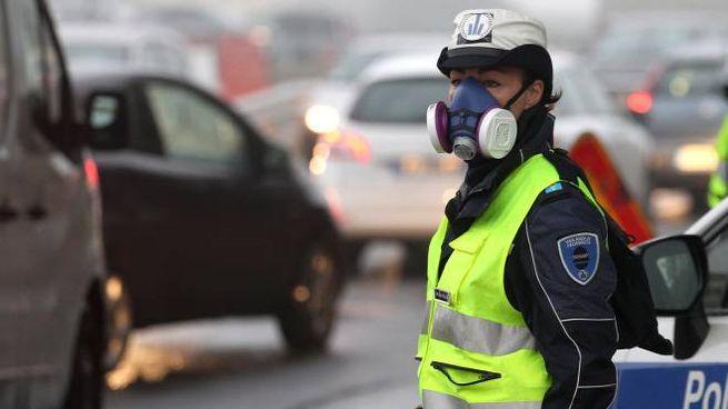 Una vigilessa con mascherina e filtri speciali in mezzo al traffico