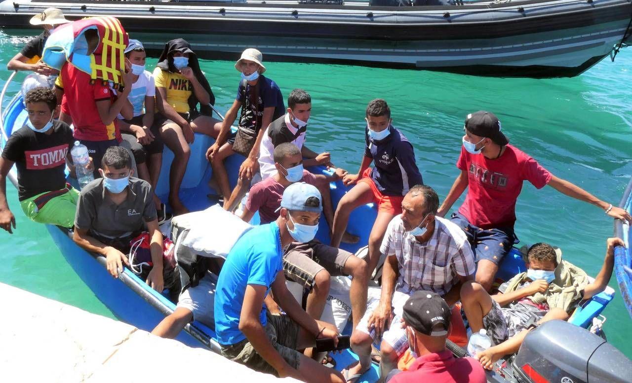 Un gruppo di migranti mentre sbarcano a Lampedusa: dopo il periodo di lockdown, gli arrivi sulle coste. sono ripresi