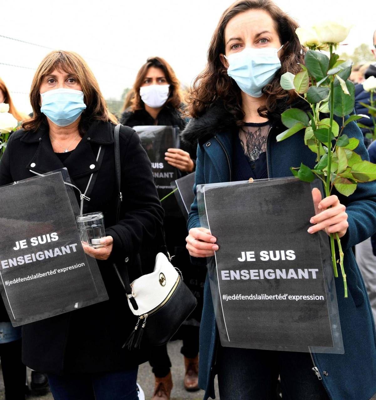 Un corteo di persone sfila con il cartello 'Io sono un professore' nel paese dove è avvenuto l'omicidio
