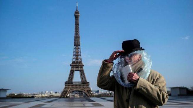 Parigi, un uomo si copre con una busta di plastica (Ansa)