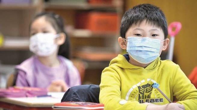 Bambini con la mascherina al banco di scuola