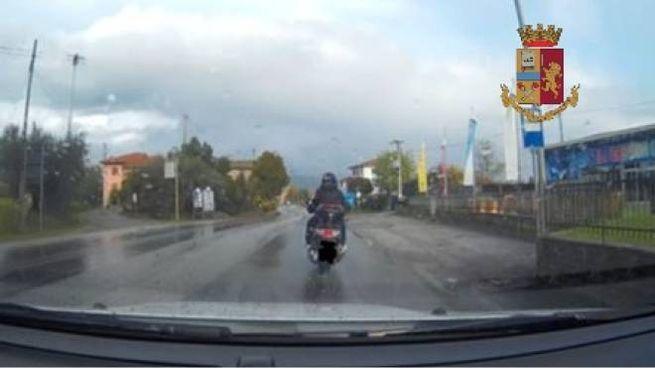 Lo scooter dei due truffatori ripreso dalla dash cam di un'auto in sosta