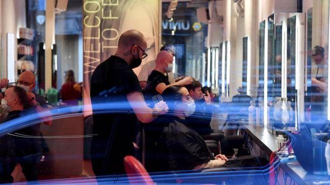 Londra, alcuni clienti in un salone di parrucchieri a Soho (Ansa)