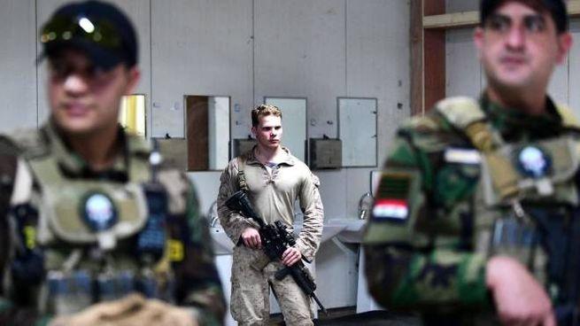 Un soldato Usa di guardia con due militari iracheni (Ansa)