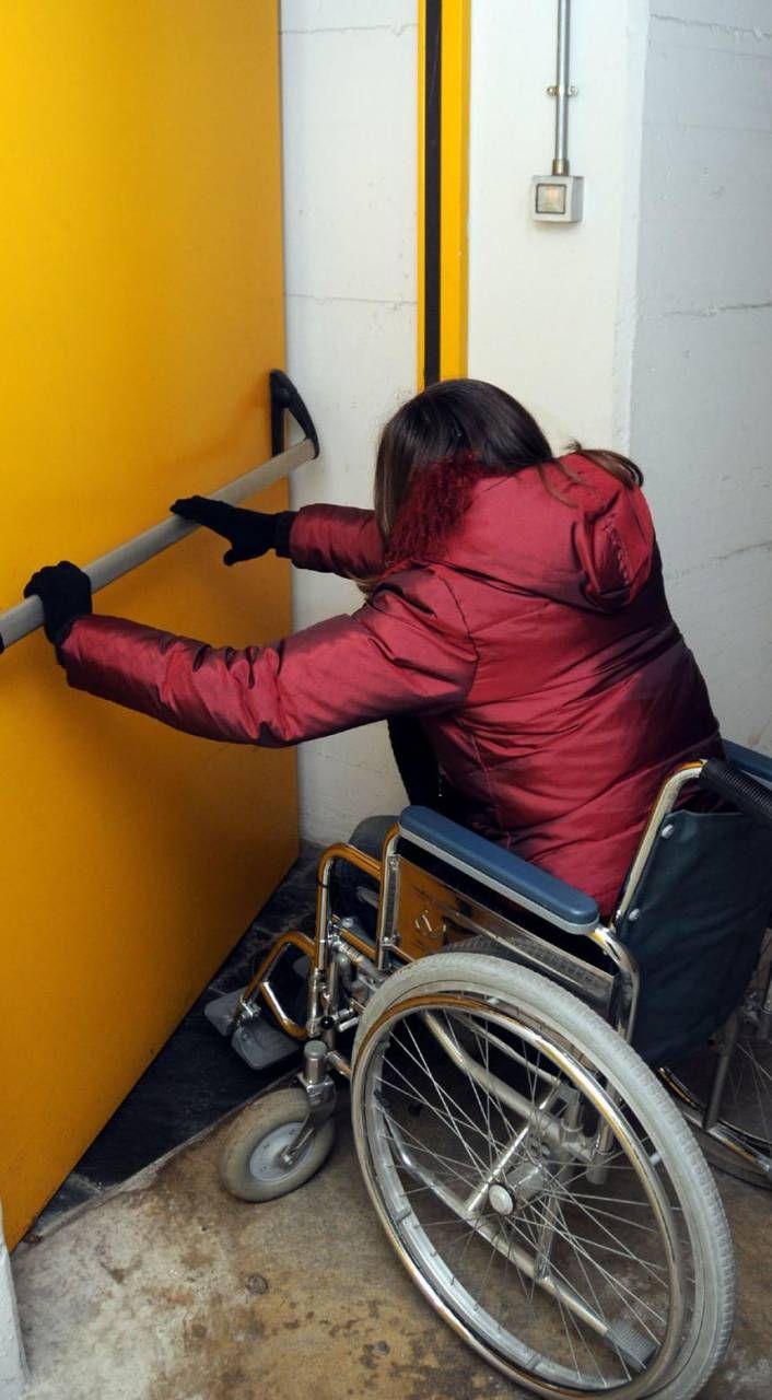 Un portatore di handicap, in carrozzina, apre una porta (foto di repertorio)