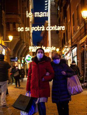 Due donne fanno shopping a Bologna, dietro le luminarie natalizie (Ansa)