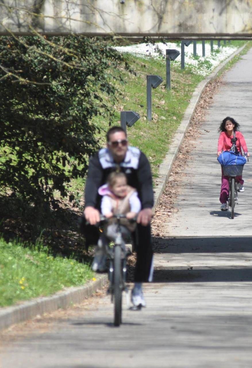 Cittadini in bici all'ingresso del parco urbano, grande polmone verde forlivese