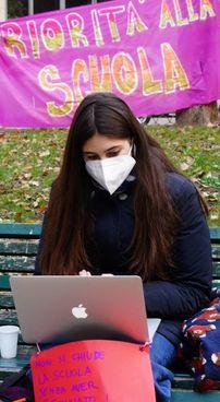 Una studentessa segue la lezione a distanza da una panchina