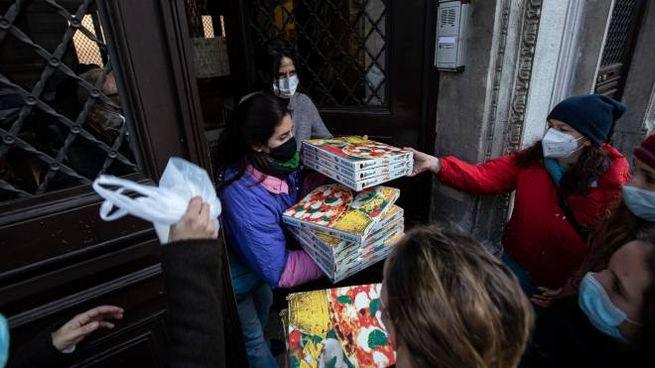 Gli studenti dell'occupazione al liceo classico Manzoni ricevono le pizze (Ansa)