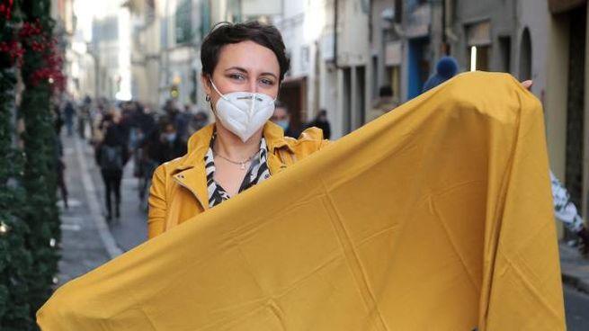 Una commerciante a Firenze mostra un drappo giallo (New Press Photo)