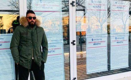 Marco Servidei davanti al. locale coperto dai volantini dell'iniziativa