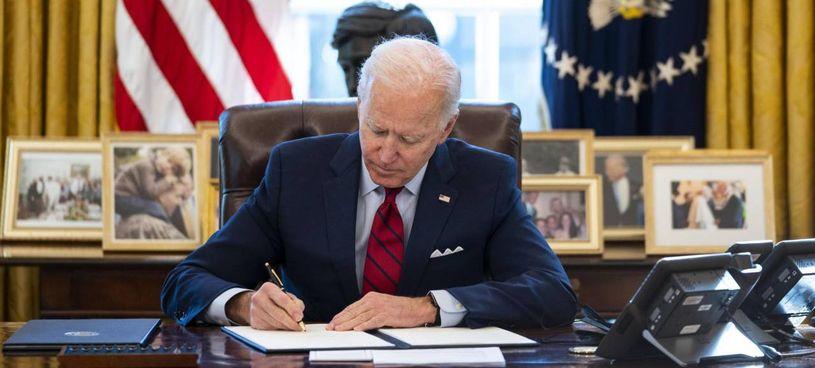 Il presidente Joe Biden nel suo studio alla Casa Bianca mentre firma le azioni esecutive che modificano alcune leggi di Trump