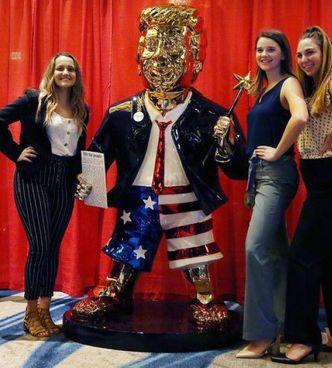 Sostenitrici di Donald Trump con la statua dorata dell'ex presidente all'ingresso del Cpac di Orlando