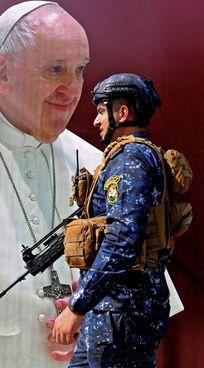 Un militare iracheno davanti a un'immagine del Papa a Baghdad