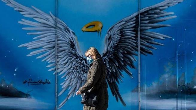 Una donna con la mascherina passa davanti a un murales in Germania (Ansa)