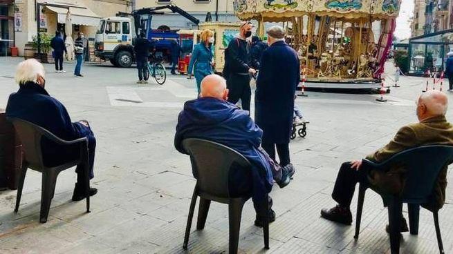 Gli anziani con le sedie in piazza