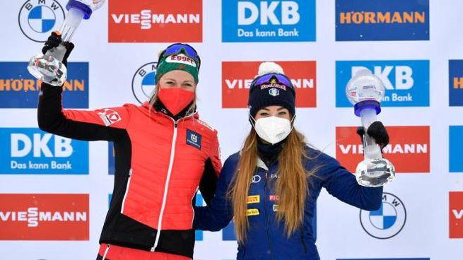Lisa Hauser e Dorothea Wierer con i loro trofei (Ansa)
