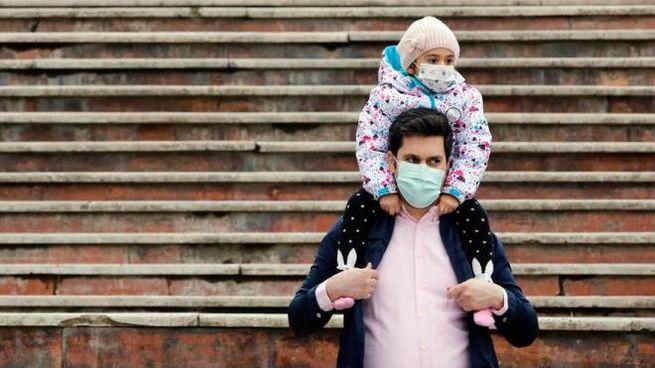 Un uomo e una bambina con la mascherina (foto Ansa)