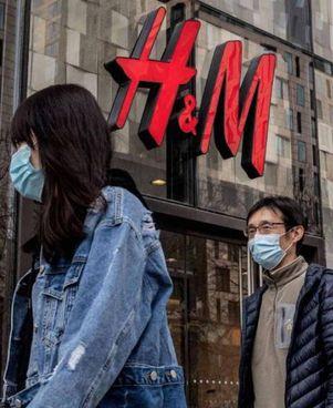 Ragazzi cinesi davanti alla vetrina di un negozio H&M in Cina. La catena svedese è nel mirino di Pechino