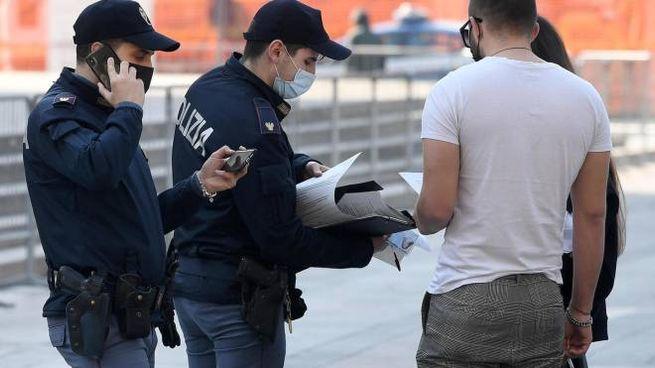 Due agenti di Poizia controlla l'autocertificazione di due persone in piazza Duomo,Milano, 30 marzo 2021. ANSA/DANIEL DAL ZENNARO