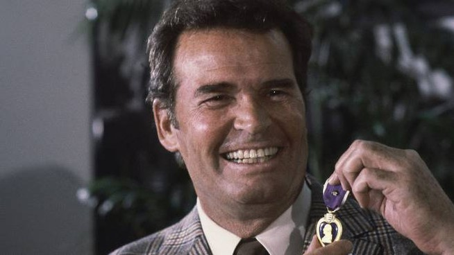 """FILE - Actor James Garner, left, smiles as he holds up the Purple Heart medal presented to him in a ceremony in this Monday, Jan. 24, 1983 file photo taken Los Angeles, Calif. Garner was wounded in April 1951 while with U.S. Forces in Korea, but his medal was never presented to him. Actor James Garner, wisecracking star of TV's """"Maverick"""" who went on to a long career on both small and big screen, died Saturday July 19, 2014 according to Los angeles police. He was 86. (AP Photo/Lennox McLendon, File)"""