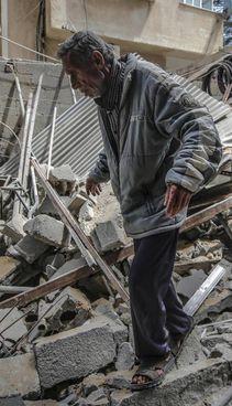 Un anziano palestinese cammina sulle macerie della propria casa