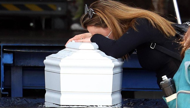 Una parente dei morti israeliani piange sulla bara bianca del piccolo Tom: aveva 2 anni, è la vittima più giovane della strage