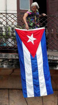 Nel centro de L'Avana una donna espone la bandiera del suo Paese