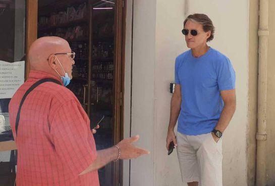 Roberto Mancini, 56 anni, in fila ieri davanti a un negozio di alimentari di Jesi. In alto a destra, nel locale dove è stato acclamato al suo ritorno nel paese natale. Il ct neo campione d'Europa non si è risparmiato tra richieste di selfie e di autografi