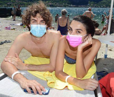 Turisti. in spiaggia con le mascherine. Oggi all'aperto. non sono obbligatorie