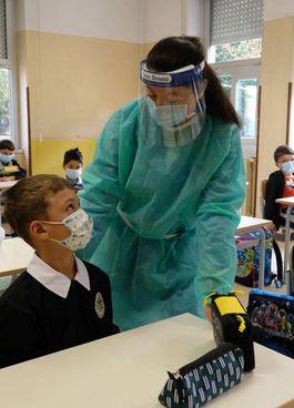 Un'operatrice sanitaria illustra i comportamenti corretti a scuola e i tamponi salivari agli studenti