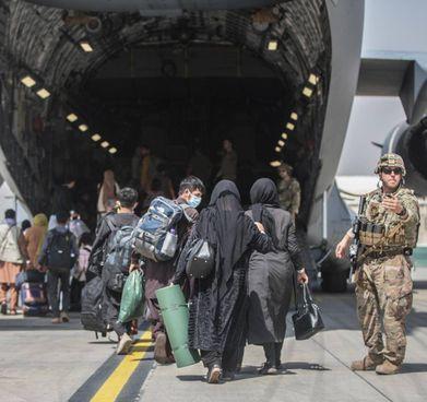 Civili afghani si imbarcano su un aereo cargo americano all'aeroporto di Kabul