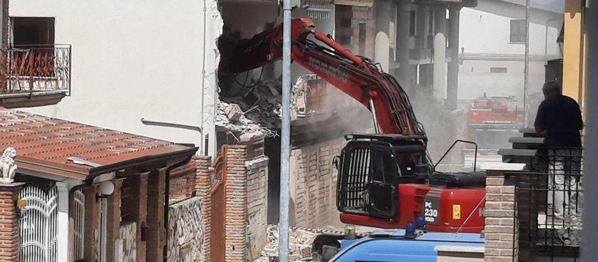 Una ruspa demolisce i muri dell'immobile di via Ancona, non lontano dal centro