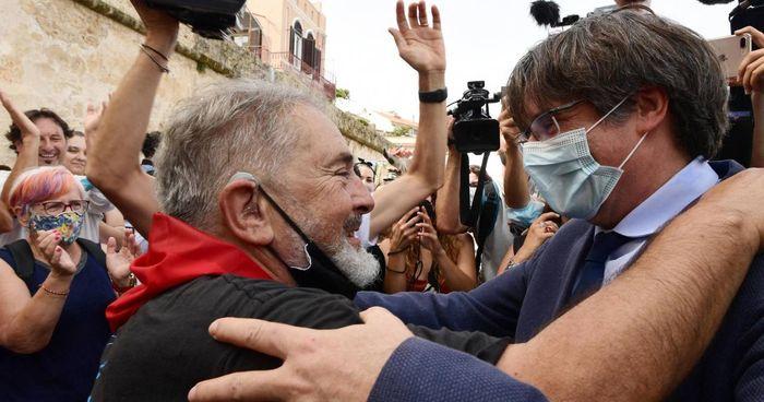 Sopra: Carles Puigdemont, 58 anni, abbracciato da un cittadino.. Sotto: il sindaco Mario Conoci accoglie nella sede di rappresentanza del Comune di Alghero, Laura Borras, presidente del parlamento catalano e il leader indipendentista
