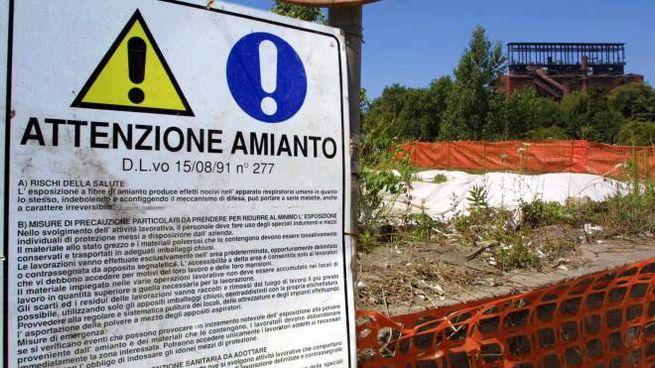 Un cartello che segnala ingenti quantitativi di amianto sepolti sotto un lieve strato di terreno, scoperti a poca distanza dai cancelli dell'ex stabilimento dell'Eternit a Bagnoli, in un'immagine del luglio 2001    CIRO FUSCO/ANSA