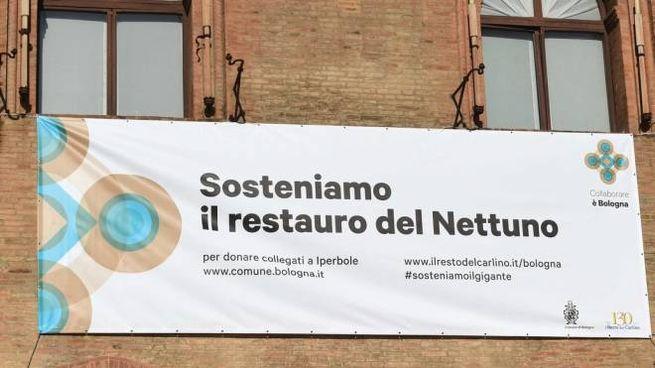 Bologna, lo striscione 'Sosteniamo il restauro del Nettuno' affisso sulla facciata del Comune