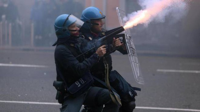DISORDINI Due agenti della polizia durante le devastazione dei No Expo a Milano. Undici feriti tra le forze dell'ordine (Ansa)