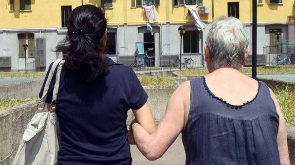 Una badante porta a passeggio un'anziana
