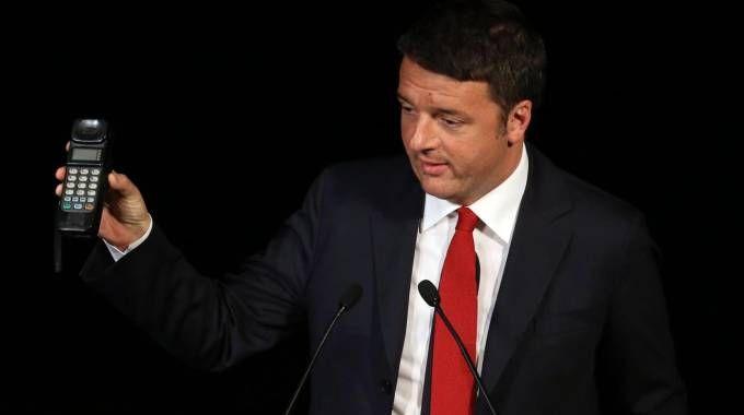 Matteo Renzi mostra un telefonino anni '90 alla platea di Milano